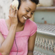African woman listening to headphones outdoors — Stock Photo