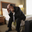 Middle-aged businessman sitting on bed in hotel room — Stock Photo