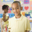 African boy painting in classroom — Stock Photo