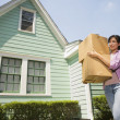 Hispanic woman carrying moving boxes — Stock Photo