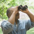 African man looking through binoculars outdoors — Stock Photo #23332092