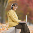Hispanic woman using laptop outdoors with headphones — Stock Photo