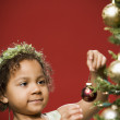 Young African girl putting ornament on Christmas tree — Stock Photo