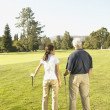 Asian couple on golf course — Stock Photo