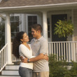 Hispanic couple hugging in front of house — Stock Photo