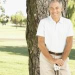 Senior man next to tree on golf course — Stock Photo #23332206