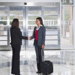 Businesswomen shaking hands in lobby — Stock Photo