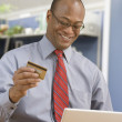 African businessman buying merchandise online with credit card — Stock Photo