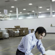 Businessman writing on pad in warehouse — Stock Photo