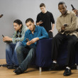 Group of multi-ethnic men text messaging on cell phones — 图库照片