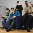 Group of multi-ethnic men text messaging on cell phones — Stock Photo