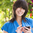 Mixed race woman text messaging on cell phone — Stock Photo