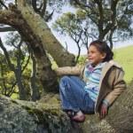 Hispanic girl climbing tree — Stock Photo #23332320
