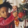 African girl putting ornament on Christmas tree — Stock fotografie