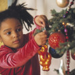 African girl putting ornament on Christmas tree — Stock Photo