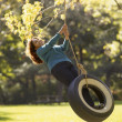 Hispanic woman swinging on tire swing — Stock Photo #23332384