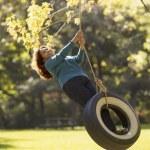 Hispanic woman swinging on tire swing — Stock Photo