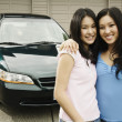 Asian sisters hugging in driveway — Stock Photo