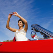 Mixed race woman taking photograph from red convertible — Stock Photo