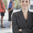 Businesswoman with co-workers in background — Stock Photo