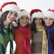 Smiling teenage girls wearing scarves and Santa hats — Stock Photo