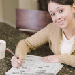 Hispanic woman searching newspaper classified ads — Stock Photo
