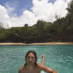 Pacific Islander man paddling surfboard in water — Stock Photo #23332678