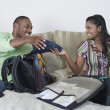Multi-ethnic couple packing for vacation — Stock Photo
