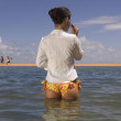 Pacific Islander woman talking on cell phone in ocean — Stock Photo