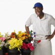 Surprised African florist with cart of flowers — Stock Photo