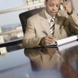 African businessman writing on notepad — Stock Photo