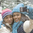 Multi-ethnic girls in snow taking self-portrait — Stock Photo