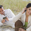 Hispanic couple talking on cell phones at beach — Stock Photo