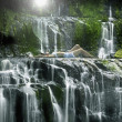 Pacific Islander woman laying in pool near waterfall — Stock Photo