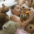 Hispanic girl sleeping in bed surrounded by stuffed animals — Stock Photo
