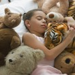 Hispanic girl sleeping in bed surrounded by stuffed animals — Stok fotoğraf
