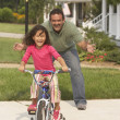 Stock Photo: Hispanic father helping daughter ride bicycle