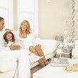 Hispanic family sitting on sofa at Christmas — Stok fotoğraf
