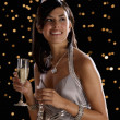 Hispanic woman drinking champagne on New Year's Eve — Stock Photo