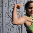 Hispanic woman flexing biceps — Stock Photo