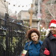 African man in santa hat walking outdoors with girlfriend — Stock Photo