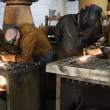 Welders working with torches in foundry — Stock Photo