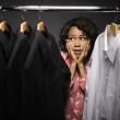 Uncertain mixed race woman looking at shirts in closet — Stock Photo #23333110