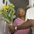 Senior African man giving flowers to wife in doorway — Stock Photo #23333138