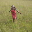 Africwomrunning through field — Stock Photo #23333152