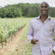 African man with wineglass in vineyard — Stock Photo