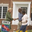 African couple shaking hands with real estate agent — Stock Photo