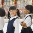 Multi-ethnic school children in uniforms in a row outdoors — Stock Photo