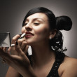 Hispanic woman applying lipstick with compact mirror — ストック写真