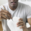 African man eating out of Chinese take out box — Stock Photo
